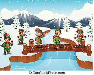 Happy kid wearing elf costume on the bridge in the snowing hill