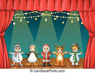 Happy kids wearing Christmas costumes performing on stage