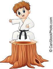 Little boy doing karate on tree stump