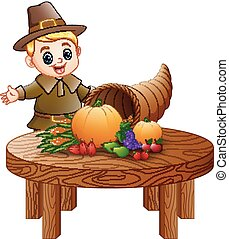 Pilgrim boy with cornucopia of fruits and vegetables on round wooden table