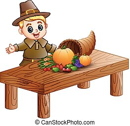 Pilgrim boy with cornucopia of fruits and vegetables on wooden table