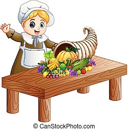 Pilgrim girl with cornucopia of fruits and vegetables on wooden table