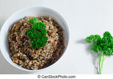 Vegan buckwheat porridge topped with fresh parsley in a bowl on a white table. Healthy breakfast.