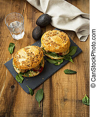 Vegan burgers with falafel chickpeas balls, avocado and spinach leaves
