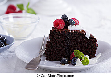 Vegan chocolate cake with berries and coconut on top