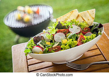 Vegan Healthy fresh leafy green salad in a white ceramic bowl on a wooden picnic table in the sunshine at a summer garden barbecue