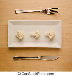 Vegan low-carb diet raw cauliflower on rectangular plate