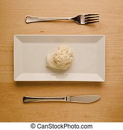 Vegan low-carb diet raw cauliflower on rectangular plate