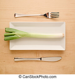 Vegan low-carb diet raw uncut spring onion on rectangular plate