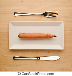 Vegan low-carb diet raw unpeeled carrot on plate with cutlery