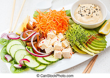 Vegan lunch salad with tofu, hummus and vegetables.