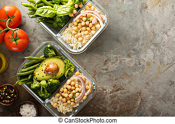 Vegan meal prep containers with cooked rice and chickpeas -...