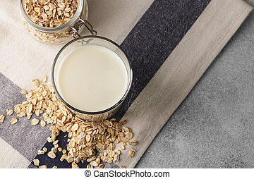 Vegan oat milk with oat flakes close up