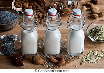 Three bottles of vegan plant milk (almond milk, poppy seed milk and hemp seed milk) on a wooden table, with shelled and unshelled almonds, poppy seeds, hemp seeds and dates in the background