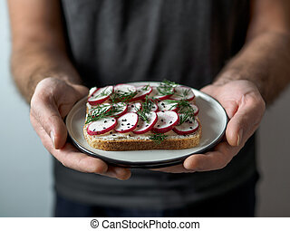 Vegan sandwich with radish in male hands
