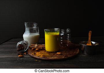 Vegan turmeric latte in a glass, almond milk, spices on dark rustic background, closeup view