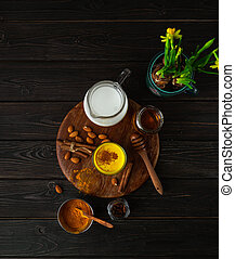 Vegan turmeric latte in a glass, almond milk, spices, potted yellow duffodils on dark rustic background, top view