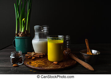 Vegan turmeric latte in a glass, almond milk, spices, potted yellow duffodils on dark rustic background, closeup view