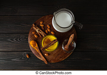Vegan turmeric latte in a mug, almond milk, spices on dark wooden background, top view