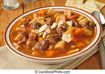 A bowl of vegetable beef soup on a rustic wooden table
