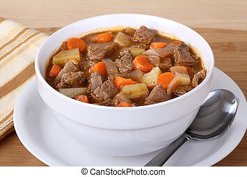 Bowl of vegetable beef soup with carrots and potatoes