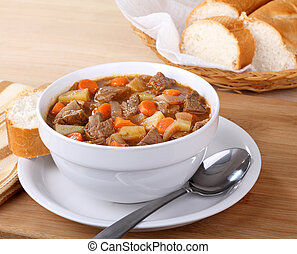 Bowl of vegetable beef soup with sliced bread