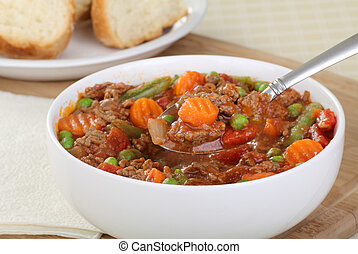 Bowl of vegetable beef soup with spoonful of soup