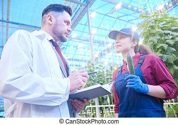 Vegetable Breeder Talking to Worker in Farm