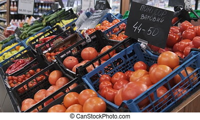 Vegetable department in a supermarket. Containers with tomatoes, cucumbers and bell peppers with price tags. The inscription on the price tag - Tomatoes. Close-up. 4K.