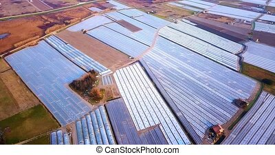 Vegetable field plots with hotbeds under thick foil in farmland at bright morning sunlight in spring season aerial view