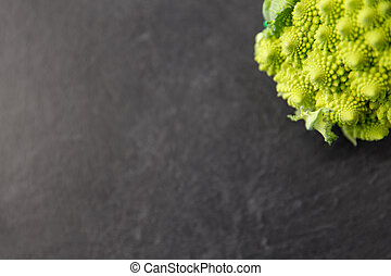 vegetable, food and culinary concept - close up of romanesco broccoli on slate stone background