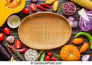 Vegetable frame. Wicker plate on a wooden background. Menu design. Copy Place.