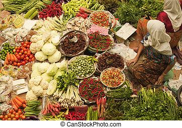 Vegetable market. - Muslim woman selling fresh vegetables at...