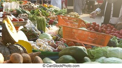 Heaps of ripe fresh vegetables and exotic fruits placed on stall on sunny day on street market