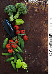 Vegetable mix of garden cherry tomatoes, cucumbers, paprikas, eggplant, broccoli on rusty metal grunge background, top view.