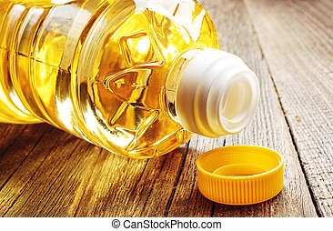 Vegetable oil in plastic bottle closeup on the old wooden ...