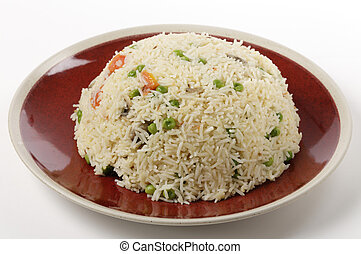 A moulded dome of vegetable pilau rice on a plate ready for serving, made with garlic, sliced mushrooms, chopped tomato, cumin seeds and basmati rice.