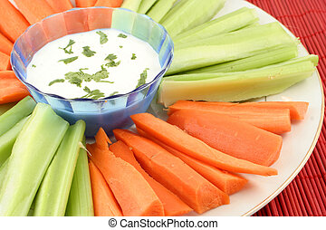 fresh celery and carrots on plate with bowl of dip