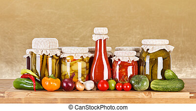 Various pickles in glass bottle surrounded by fresh vegetables