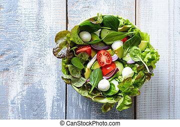 vegetable salad in bowl on wooden background