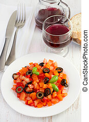 vegetable salad on the plate with glass of red wine