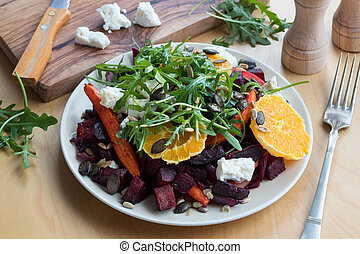 Vegetable salad with baked beets and carrots and fresh arugula