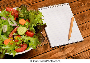 Vegetable salad with notepad