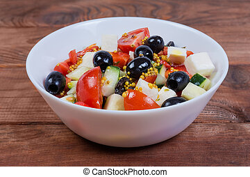 Vegetable salad with soft cheese in bowl close-up