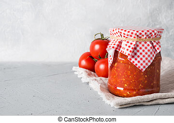 Vegetable sauce adjika with tomatoes, garlic, bell peppers in jar.