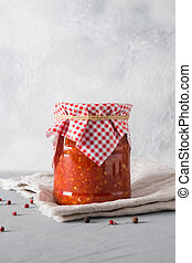 Vegetable sauce adjika with tomatoes, garlic, bell peppers in jar on light background.