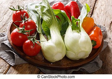 Vegetable set of fresh baby bok choy, tomatoes and peppers close-up on a plate. horizontal