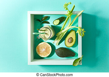 Vegetable smoothies from avocado, asparagus, spinach, cucumber, celery with flax seeds in square frame on a green kitchen table.