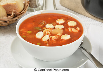 A bowl of vegetable beef soup with dinner rolls