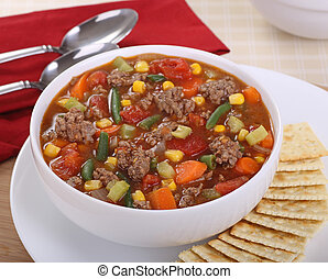 Bowl of vegetable and beef soup with crackers